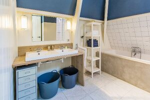 Small chest of drawers and blue baskets below simple washstand with twin sinks on wooden frame next to bathtub with concrete surround in converted attic