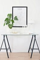 Houseplant, candlestick and Panton lamp on delicate console table made from trestles and glass panel