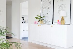 Houseplant, pineapple table lamp and pictures leaning against wall on top of white sideboard in hallway