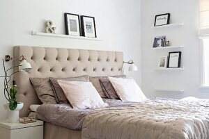 Double bed with beige, button-tufted headboard in white bedroom with pictures on narrow shelves