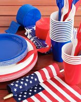 Paper plates, paper cups, plastic cutlery and streamers in red, white and blue for the fourth of July