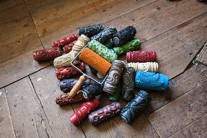 Colourful pattern paint rollers with various patterns on wooden surface