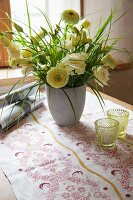 Vase of flowers and table runner printed with traditional floral motif