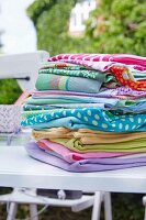 A pile of fabrics on a table outdoors