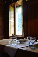 Glasses, carafe and plates on rustic dining table next to window in wood-clad dining room