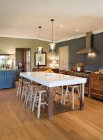 Large dining table and wooden stools in cosy kitchen