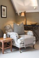 Armchair with toile de jouy upholstery in indirect lighting