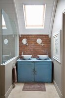 Battered blue washstand in niche under sloping ceiling