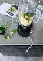 Pineapple pieces and peppermint leaves in a blender