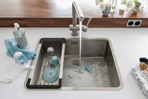 A white work surface with a built-in sink with a drainer and a tap