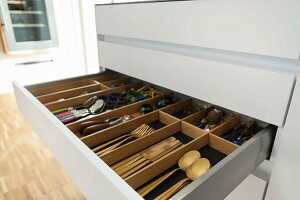 An open cutlery drawer in a kitchen cupboard