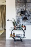 Arc Deco sideboard used as minibar below hat-shaped designer pendant lamp