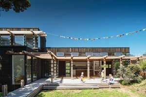 View from garden to mother and children on wooden terrace with pergola