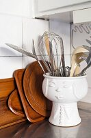 Kitchen utensils in face pot in front of wooden plates