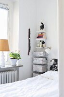 Magazines stacked on vertical bookshelves next to bed