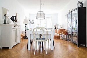 Dining table and vintage furniture on herringbone parquet flooring