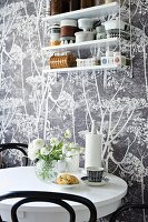 Round table and String shelves hung on floral wallpaper