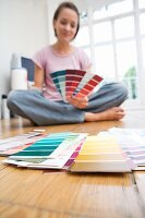 Woman sitting on floor looking at paint colour charts