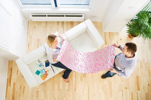 Young pair holding strip of wallpaper in new apartment