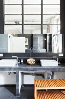 Twin countertop sinks in minimalist bathroom of loft apartment with industrial interior window