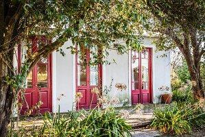 Blick durch Bäume auf Haus mit roten Türen