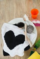 A hand-knitted dishcloth with a heart design made of cotton yarn