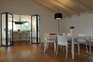 Dining table and view into kitchen through modern folding door