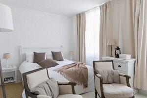 Elegantes Landhaus-Schlafzimmer mit Armlehnsesseln