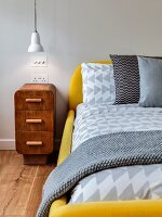 Antique bedside cabinet next to modern bed with yellow upholstered frame