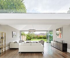 Living room with skylight and glass wall leading to garden