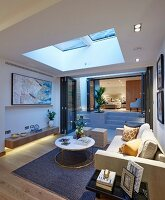 Illuminated living room with skylight and view into bedroom