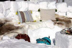 Winter-Picknick mit Sitzbank aus Schnee und Fellen