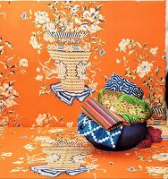 A bowl of colourful ethnic textiles on orange fabric
