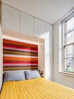 Fitted cupboards and striped headboard in small bedroom