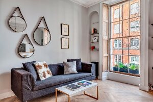 Three mirrors above grey sofa in renovated townhouse apartment