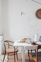 Set white dining table and wooden chairs below light-bulb lamp on wall