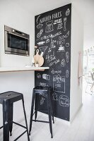 Chalkboard wall covered in drawings next to breakfast bar and bar stools