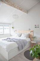 Doppelbett mit Holz-Betthaupt in hellem Schlafzimmer im Dachgeschoss