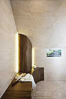 A designer bathroom with a bench and a semi-circular panel under a tiled roof slope