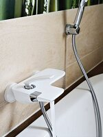 A white bath tap and a shower hose on a tiled wall