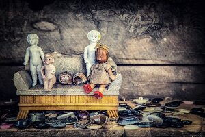 Collection of buttons and various antique dolls sitting on dolls' couch against dark background