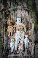 Macabre arrangement of antique dolls on wooden tray