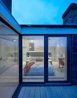 Twilight atmosphere over roof terrace with view into elegant modern bedroom