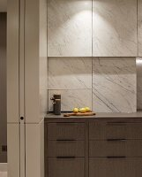 Kitchen drawers in base units below marble-clad cupboards