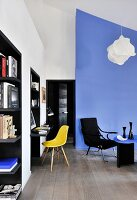 Black fitted shelves, console table, yellow classic chair and blue partition in living area