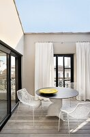Designer table and metal chairs on roof terrace