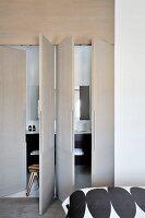 View from bedroom into bathroom hidden behind cupboard doors