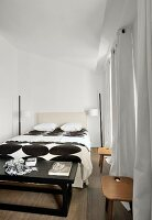 Black and white bed linen on double bed in bedroom with floor-length curtains