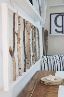 3D artwork made from birch branches above rustic wooden table