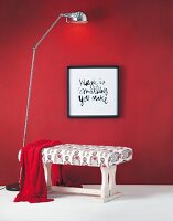 DIY bench made from former wooden coffee table arranged with framed motto on red wall and standard lamp